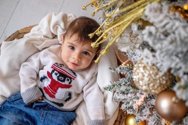 Een kind ligt in de buurt van de kerstboom met kerstaccessoires nieuwjaar en kerstconcept