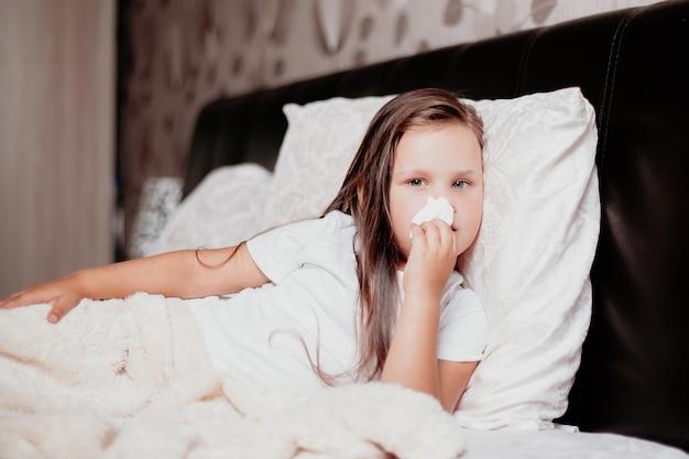 Een kind ligt op een kravat en veegt snot af met servetten, de tweede golf van het covid-19-virus.