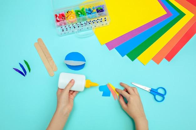 Een kind lijmt gekleurd blauw papier met lijm aan de tafel. papierambachten voor kinderen.