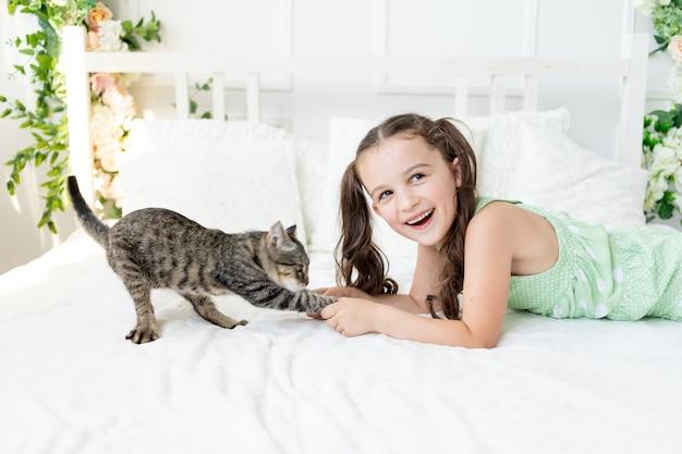 Een kind martelt een dier, een klein meisje met een kat ligt op het bed, het concept van de vriendschap van een kind met dieren
