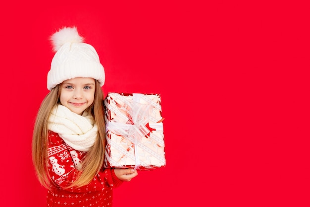 Een kind meisje in een winter muts en trui met geschenken op een rode monochrome geïsoleerde achtergrond verheugt zich en glimlacht, het concept van nieuwjaar en kerstmis, ruimte voor tekst