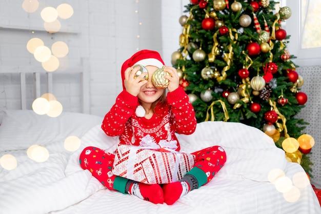 Een kind meisje met kerstballen op haar oren bij de kerstboom in een rode trui en kerstman hoed op oudejaarsavond in een wit bed glimlachend, gek rond en lachen met een cadeau