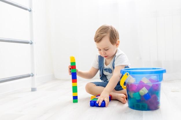 Een kind met een aannemer thuis, een schattige jongen speelt of verzamelt een gekleurde aannemer