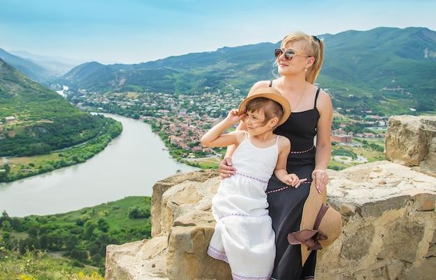 Een kind met een moeder op de achtergrond van de aantrekkelijkheden van georgië