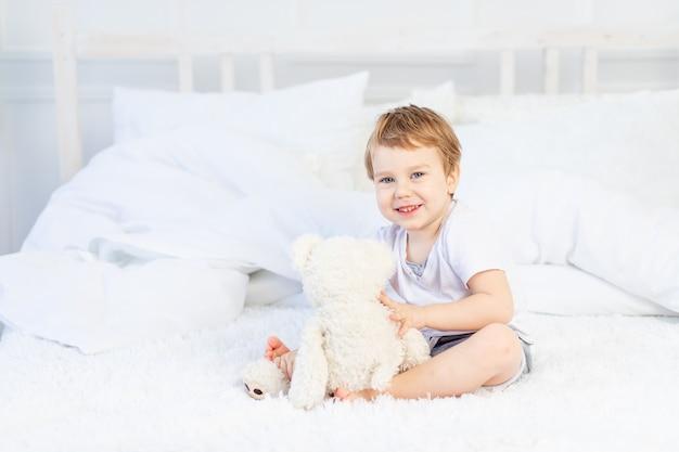 Een kind met een teddybeer op het bed thuis speelt en lacht