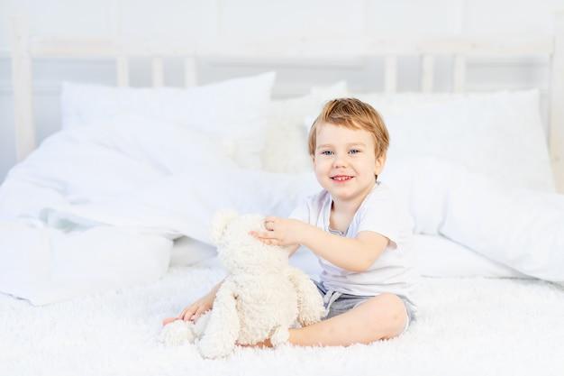 Een kind met een teddybeer op het bed thuis speelt en lacht.