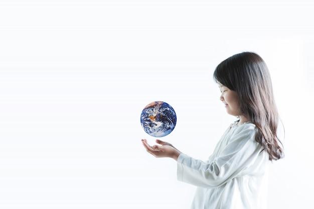 Een kind met een witte heeft de aarde op zijn hand en kijkt er vrolijk naar.