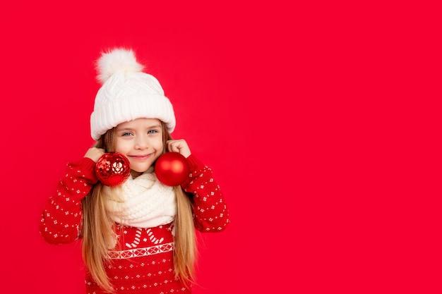 Een kind met kerstboomballen op een rode monochrome achtergrond verheugt zich en lacht de concep