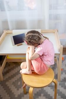 Een kind met witte tablet. kid op online onderwijs, e-learning tijdens quarantaine. kid horloges tekenfilms op tablet.