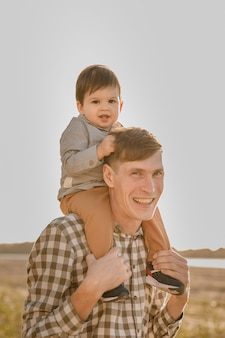 Een kind om de nek van zijn vader. loop langs het water. baby en papa tegen de hemel.