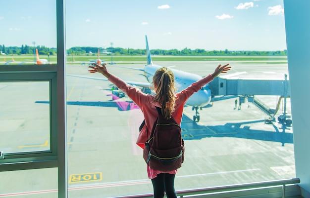 Een kind op de luchthaven kijkt naar het vliegtuig. selectieve aandacht. kind.