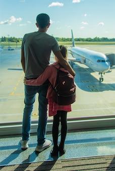 Een kind op de luchthaven kijkt naar het vliegtuig. selectieve aandacht.