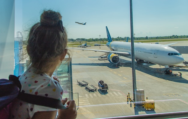 Een kind op de luchthaven op de achtergrond van het vliegtuig