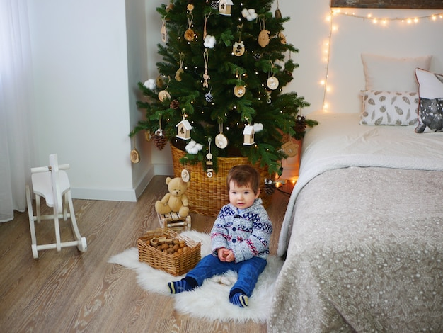 Een kind op de vloer bij de kerstboom en nieuwjaarsversieringen