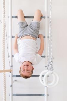 Een kind op de zweedse muur sport thuis, een jongen beklimt een ladder met een touw, het concept van sport en gezondheid