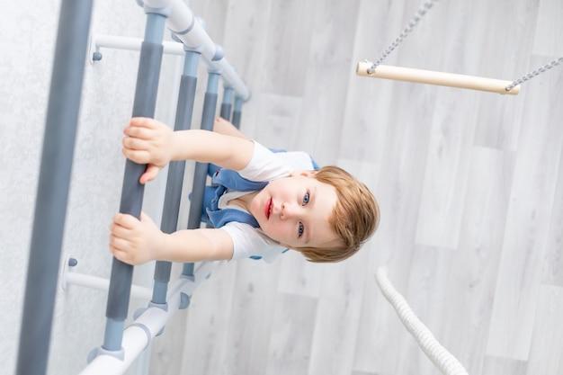 Een kind op de zweedse muur sport thuis, een jongen beklimt een ladder met een touw, het concept van sport en gezondheid.
