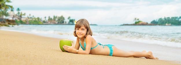 Een kind op het strand drinkt kokos