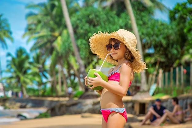 Een kind op het strand drinkt kokosnoot. selectieve aandacht. natuur.