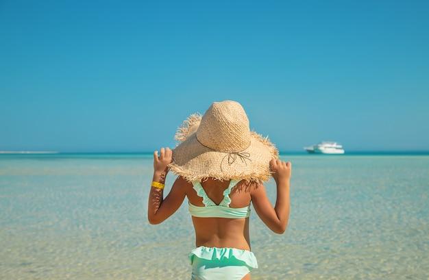 Een kind op het strand in de buurt van de zee.
