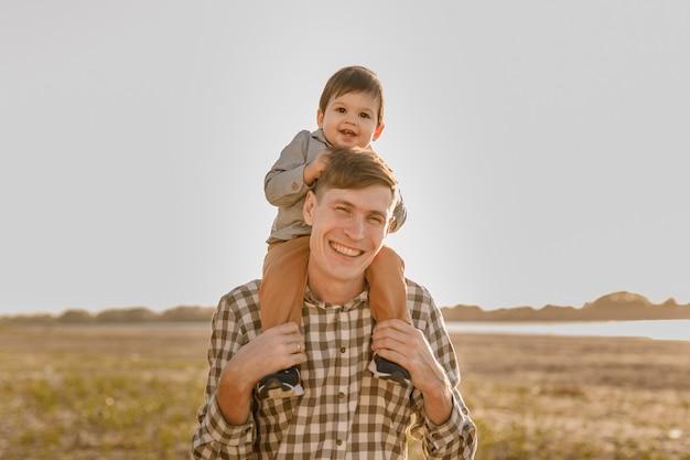 Een kind op zijn vaders nek. loop langs het water. baby en papa tegen de hemel.