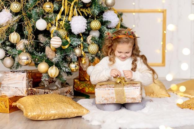 Een kind pakt thuis een nieuwjaarscadeau uit bij een kerstboom met een gouden decor