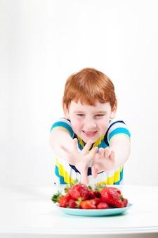 Een kind reikt naar aardbeien aan de overkant van de tafel om zoete bessen te eten