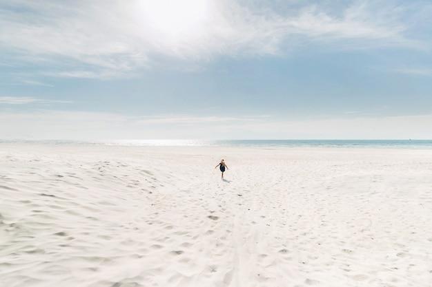 Een kind rent bij zonnig weer langs een wit strand naar de baltische zee. een klein meisje rent over het sneeuwwitte zand om de zee te ontmoeten. litouwen.