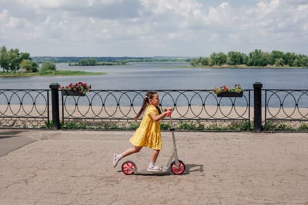 Een kind rijdt snel op een scooter langs de dijk langs de baai en vermaakt zich tijdens een familieweekend...