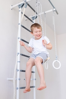 Een kind schommelt op een schommel aan de zweedse muur en doet thuis aan sport, het concept van sport en gezondheid