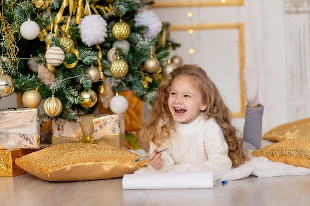 Een kind schrijft een brief voor de kerstman onder een met goud versierde kerstboom