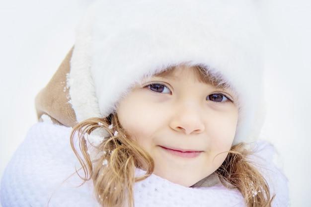 Een kind speelt in de sneeuw in de sneeuw. selectieve aandacht.