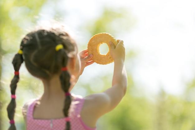 Een kind speelt met brood in de zon.