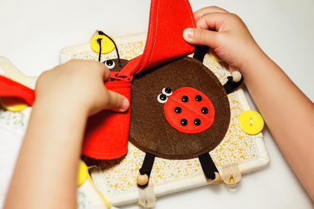 Een kind speelt met een educatief speelgoed rood lieveheersbeestje gemaakt van vilt montessori concept vroege educatie