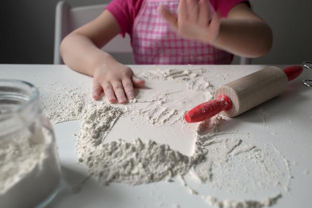 Een kind speelt met meel. het meisje bereidt pannekoeken voor.