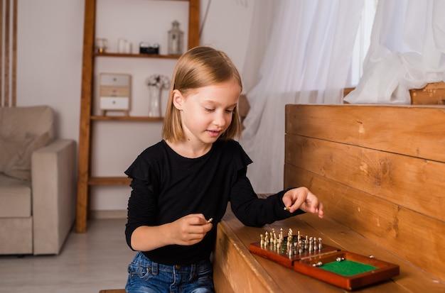 Een kind speelt schaak in een kamer. intellectuele ontwikkeling
