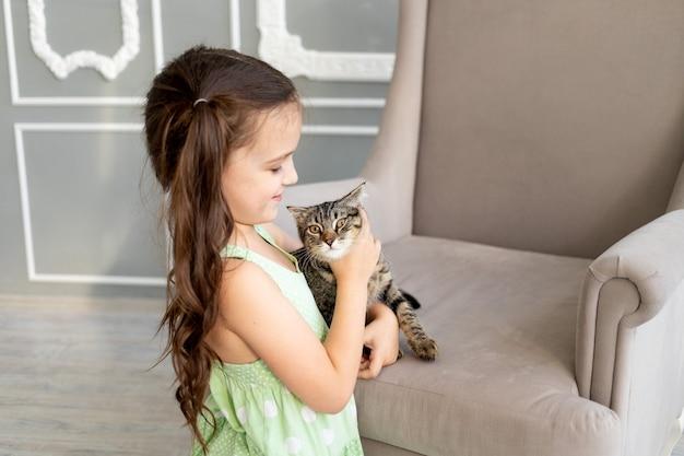 Een kind speelt thuis met een kat, een klein meisje houdt een kat in haar armen, het concept van de vriendschap van een kind met dieren