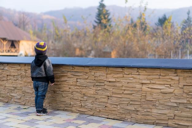 Een kind staat bij het hek en kijkt weg