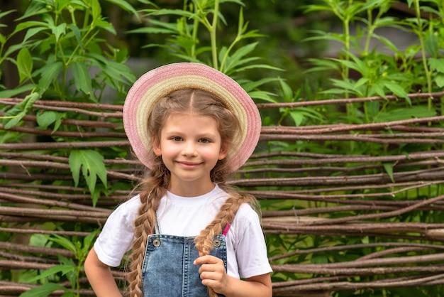 Een kind staat tegen een rieten hek.
