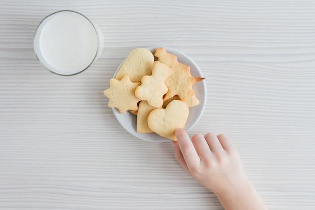 Een kind steelt van een bord versgebakken zelfgemaakte koekjes