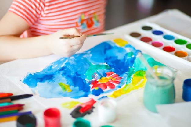 Een kind tekent bloem met gekleurde verf op het papier.