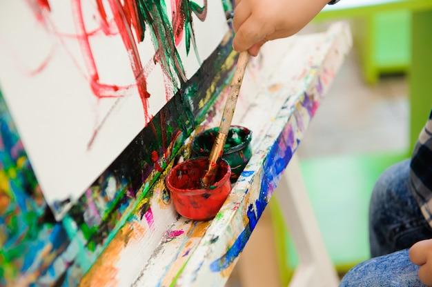 Een kind tekent een schilderij op kunstles