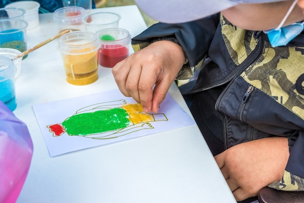 Een kind tekent een tekening met gekleurd zand in de open lucht in het park