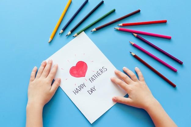 Een kind trekt een kaart met potloden voor vaderdag