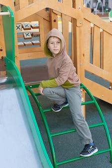 Een kind van 6-7 jaar speelt op een buitenspeeltuin. kinderen spelen op de binnenplaats van een school of kleuterschool. een actief kind op een kleurrijke glijbaan en schommel.