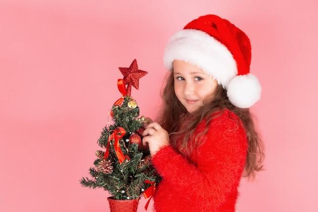 Een kind versiert de kerstboom met kerstspeelgoed