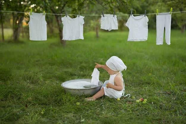 Een kind wast vrolijk zijn kleren in de wasbak. spuit water en schuim uit het wassen van kleren.