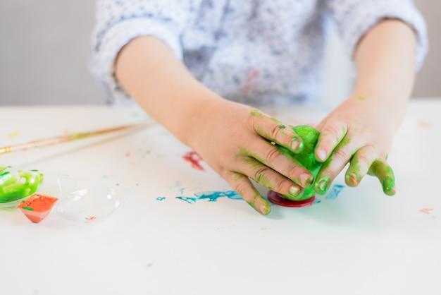 Een kind zet een groen paasei op een standaard met zijn handen gekleurd met verf op een witte tafel.