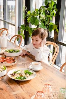 Een kind zit aan een tafel met voedsel