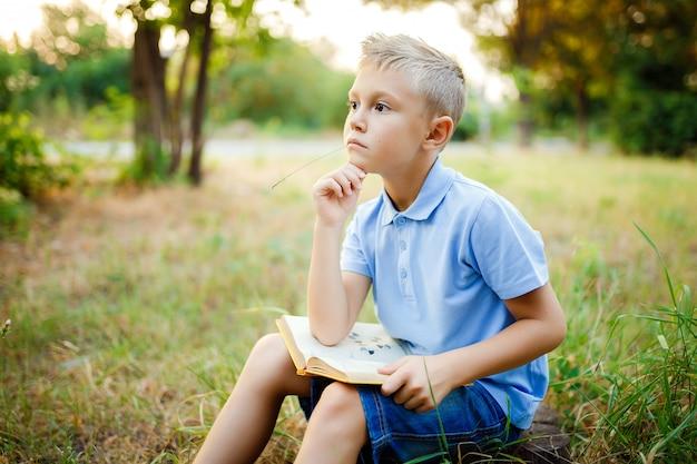 Een kind zit in het bos met boek op de knieën en kijkt weg.