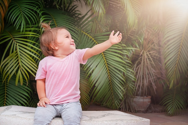 Een kind zit op een bankje tegen palmbomen